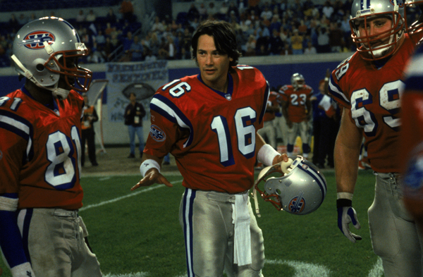 UNSPECIFIED - APRIL 18: Full shot of Keanu Reeves as quarterback Shane Falco in uniform, standing in huddle, holding helmet and talking to players. (Photo by Ron Phillips/Warner Bros./Getty Images)